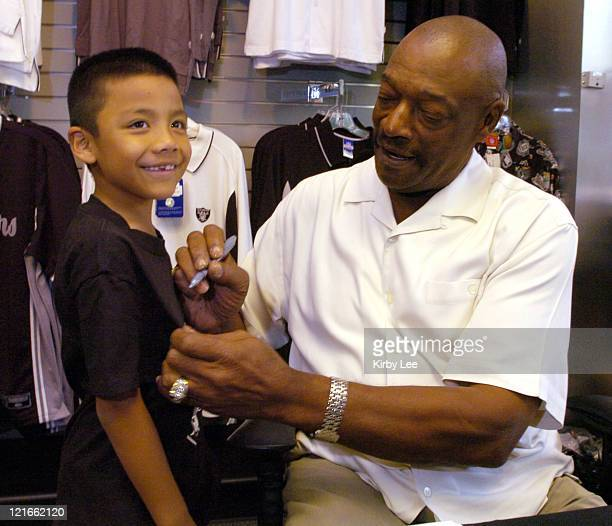 Otis Sistrunk a 1974 Pro Bowl defensive lineman and member of the Oakland Raiders Super XI championship team signs an autograph at The Raider Image...