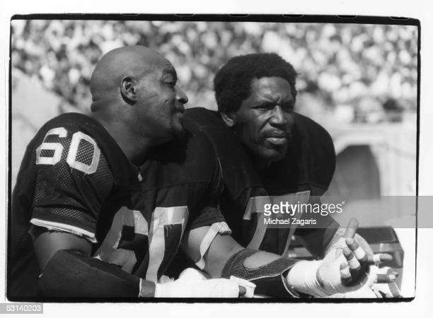 Otis Sistrunk and Bubba Smith of the Oakland Raiders sit on the sideline during the game against the Kansas City Chiefs at the Oakland Alameda...