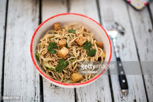 Otsu salad with soba noodles, tofu, cucumber, sesame, spring onion and coriander in bowl