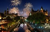 A colour image featuring a summer fireworks display festival in downtown Ottawa Canada. In the foreground are the Parliament Buildings, Rideau Canal a UNSECO world heritage site, and the Chateau Lauri