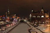 Downtown Ottawa during the holiday season with festive lights, features Parliament Hill, Chateau Laurier hotel. The Rideau Canal skate way is covered with a fresh blanket of snow.