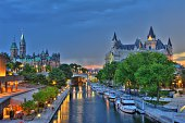 Ottawa at sunset with storm clouds advancing. Featuring Parliament Buildings, Rideau Canal a UNESCO world heritage site, Chateau Laurier Hotel, National Art Gallery and National Conference Centre. Boa