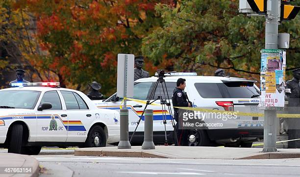 Ottawa police officers stand guard near the National War Memorial where a soldier was shot earlier in the day just blocks away from Parliament Hill...