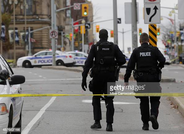 Ottawa police officers walk up Wellington St near the National War Memorial where a soldier was shot earlier in the day just blocks away from...