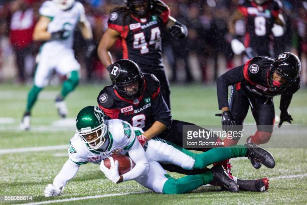 Ottawa RedBlacks defensive back Antoine Pruneau tackles a Saskatchewan Roughriders wide receiver Duron Carter during Canadian Football League action...