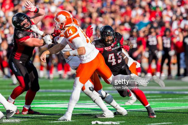 Ottawa RedBlacks defensive lineman Jonathan Newsome just misses the chance to sack BC Lions quarterback Travis Lulay during Canadian Football League...