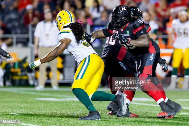 Ottawa RedBlacks offensive lineman SirVincent Rogers tries to push off Edmonton Eskimos defensive end Marcus Howard during Canadian Football League...