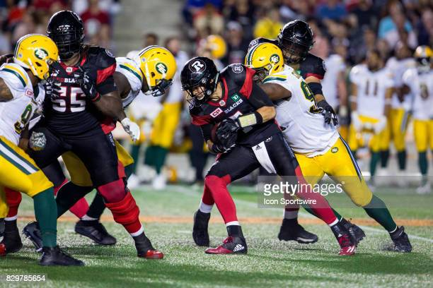 Ottawa RedBlacks quarterback Trevor Harris attempts to avoid being sacked by Edmonton Eskimos defensive lineman Euclid Cummings during Canadian...