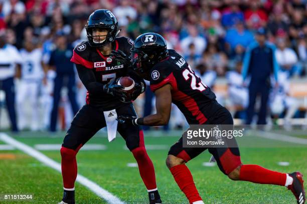 Ottawa RedBlacks quarterback Trevor Harris hands the ball off to running back Mossis Madu Jr during Canadian Football League action between the...