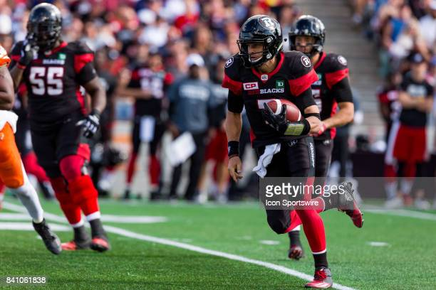 Ottawa RedBlacks quarterback Trevor Harris scrambles out of the pocket with the football during Canadian Football League action between BC Lions and...
