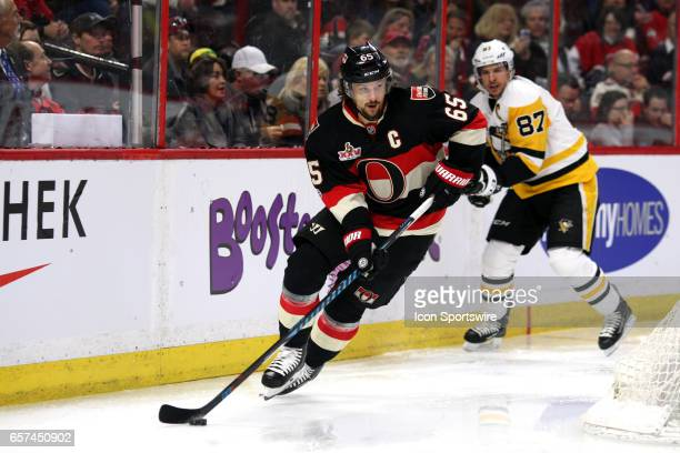 Ottawa Senators Defenceman Erik Karlsson moves the puck around the goal with Pittsburgh Penguins Center Sidney Crosby in the background during the...