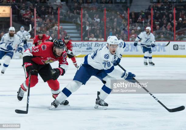 Ottawa Senators Defenceman Fredrik Claesson and Tampa Bay Lightning Centre Byron Froese chase down the puck during the NHL game between the Ottawa...