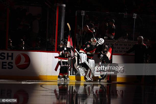 Ottawa Senators Goalie Mike Condon taps one of the Scotiabank skaters on the helmet as he makes his way onto the ice during a game between the...