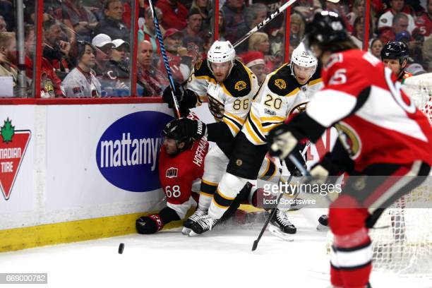 Ottawa Senators Left Wing Mike Hoffman gets knocked into the boards as Boston Bruins Defenceman Kevan Miller and Boston Bruins Center Riley Nash...