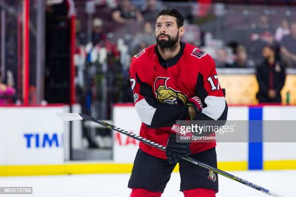 Ottawa Senators Left Wing Nate Thompson takes off a glove to pick up pucks to toss to fans during warmup before National Hockey League action between...