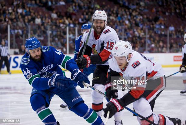 Ottawa Senators Left Wing Zack Smith looks on as Vancouver Canucks Defenceman Erik Gudbranson attempts to check Ottawa Senators Defenceman Mark...