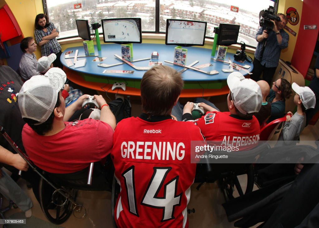 Ottawa Senators player Colin Greening #14 plays video games with young patients at the unveiling of the NHL All-Star Legacy Playroom at Children's Hospital of Eastern Ontario on January 27, 2012 in Ottawa, Canada.