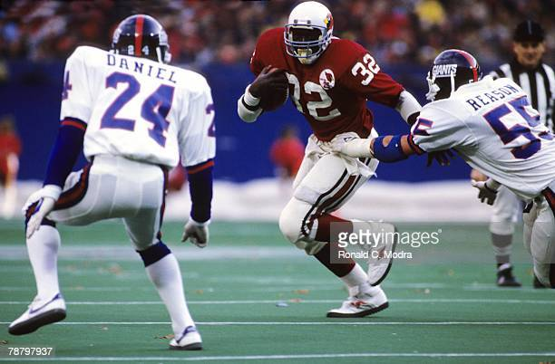Ottis Anderson of the St Louis Cardinals carries the ball during the NFL game against the New York Giants at Giants Stadium on November 18 1984 in...