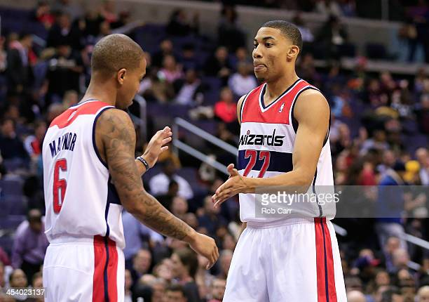 Otto Porter Jr#22 and Eric Maynor of the Washington Wizards high five during the first half against the Milwaukee Bucks at Verizon Center on December...
