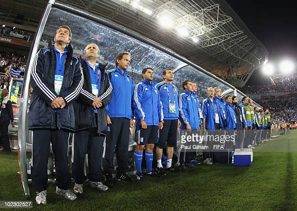 Otto Rehhagel head coach of Greece and his bench stand for the national anthems before the 2010 FIFA World Cup South Africa Group B match between...