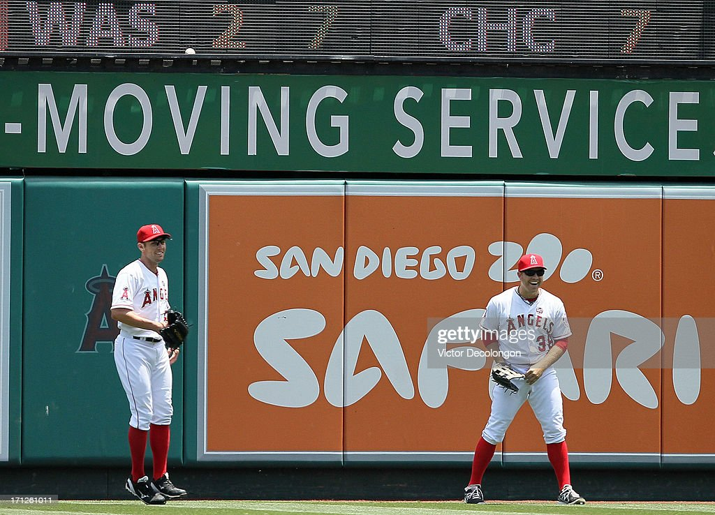 Oufielders Peter Bourjos #25 and J.B. Shuck #39 of the Los Angeles Angels of Anaheim share a laugh after the ball became lodged at the bottom of the right field scoreboard on a hit by Tony Sanchez #59 of the Pittsburgh Pirates (not in photo) in the second inning for a ground rule double during the MLB game at Angel Stadium of Anaheim on June 23, 2013 in Anaheim, California. The Pirates defeated the Angels 10-9 in ten innings.