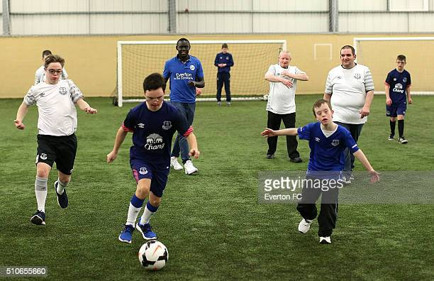 Oumar Niasse of Everton interacts with members of the Down Syndrome football team as they take part in a training session at Finch Farm on February...