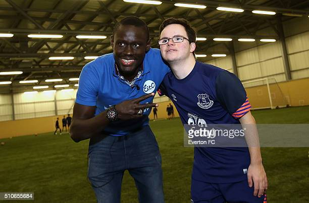 Oumar Niasse of Everton poses with members of the Down Syndrome football team as they take part in a training session at Finch Farm on February 16...