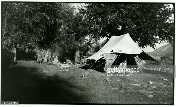 'Our camp' A British soldier sits inside a tent as his servants prepare breakfast believed to be referring to a camp in the Kashmir Valley Background...