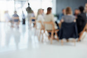 Out of focus shot of a group businesspeople sitting down during a presentation inside of a boardroom