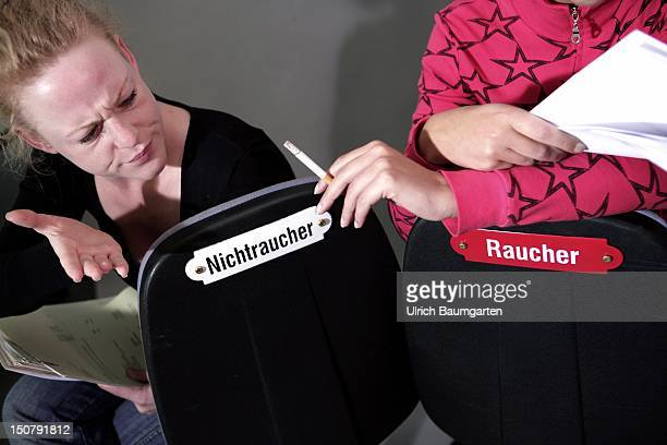 Our picture shows two female office coworkers arguing about smoking during they are sitting on office chairs with signs smoker and nonsmoker Feature...