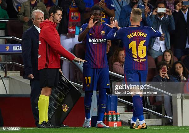 Ousmane Dembele of Barcelona shakes hands with substitute Gerard Deulofeu of Barcelona during the La Liga match between Barcelona and Espanyol at...