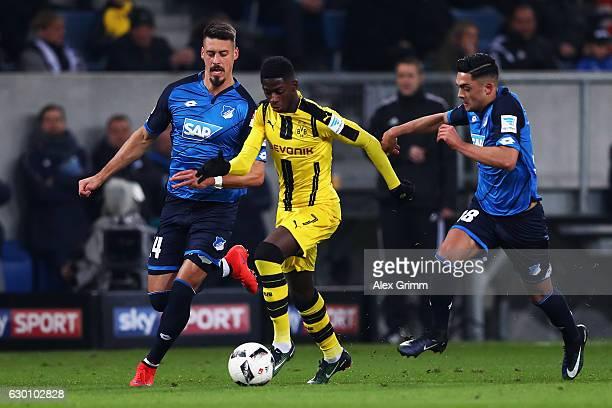 Ousmane Dembele of Borussia Dortmund battles for the ball with h14 and Nadiem Amiri of TSG 1899 Hoffenheim during the Bundesliga match between TSG...