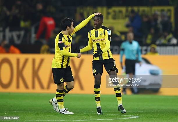 Ousmane Dembele of Borussia Dortmund celebrates scoring his team's opening goal with Shinji Kagawa during the Bundesliga match between Borussia...