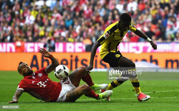 Ousmane Dembele of Borussia Dortmund escapes a challenge from Arturo Vidal of Bayern Muenchen during the Bundesliga match between Bayern Muenchen and...