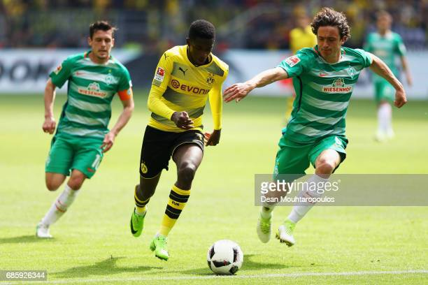 Ousmane Dembele of Borussia Dortmund gets past the tackle from Thomas Delaney and Zlatko Junuzovic of Werder Bremen during the Bundesliga match...