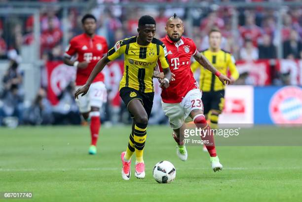 Ousmane Dembele of Dortmund and Arturo Erasmo Vidal battle for the ball during the Bundesliga match between Bayern Muenchen and Borussia Dortmund at...