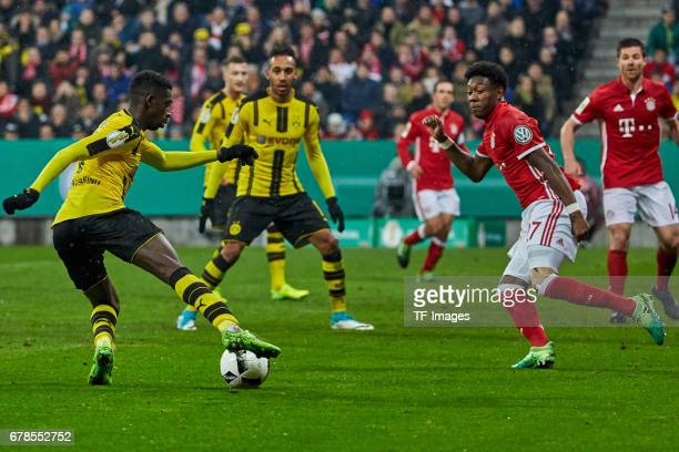 Ousmane Dembele of Dortmund and David Alaba of Bayern Munich battle for the ball during the German Cup semi final soccer match between FC Bayern...