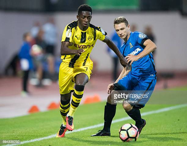 Ousmane Dembele of Dortmund is challenged by Kevin Heinz of Trier during the DFB Cup match between Eintracht Trier and Borussia Dortmund at...