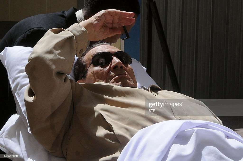 Ousted Egyptian president Hosni Mubarak gestures as he is wheeled out of a courtroom following his verdict hearing in Cairo on June 2, 2012. A judge sentenced Mubarak to life in prison after convicting him of involvement in the murder of protesters during the uprising that ousted him last year. AFP PHOTO/STR