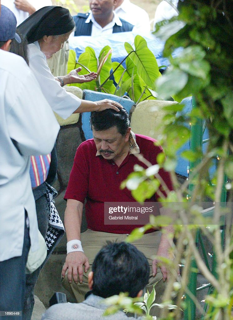 Ousted Philippine President Joseph 'Erap' Estrada receives a 'miracle bath' from Sister Gloria Ross during a spIritual healing session at the Mother...