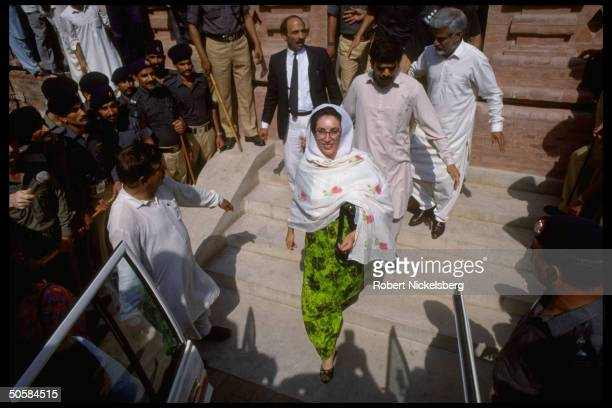 Ousted PM Benazir Bhutto leaving court after hrg re corruption charges against her descending steps lined w security police