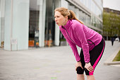 a young woman catching her breath while exercising.
