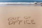 Out of office. A simple concept image written in the sand on a beautiful Hawaii beach.