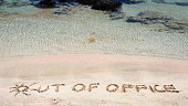 OUT OF OFFICE written in sand on a beautiful beach .Relax concept image