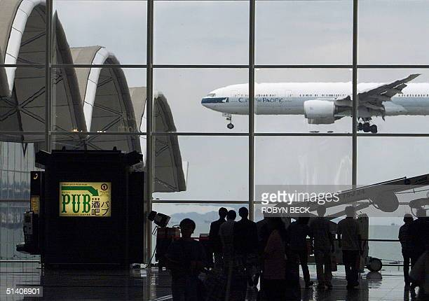 Outbound passengers watch as a Cathay Pacific jet comes in for a landing at Chek Lap Kok Hong Kong's international airport 06 July 1999 as the...