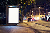 Outdoor advertising billboard or abri kiosk at nighttime in the city