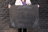 outdoor, advertisment, background concept. close up of blackboard decorated with simple patterns of leaves thar are drawn with white chalks, two female arms are holding it