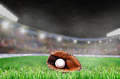 Baseball glove and ball on grass in brightly lit outdoor stadium. Focus on foreground and shallow depth of field on background with copy space. Fictitious background stadium created entirely in Photos