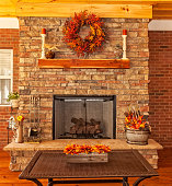 Covered backyard deck at residential house with gas fireplace, decorations for the season of autumn.