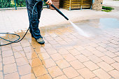 Outdoor floor cleaning with high pressure water jet - cleaning concrete block floor on terrace